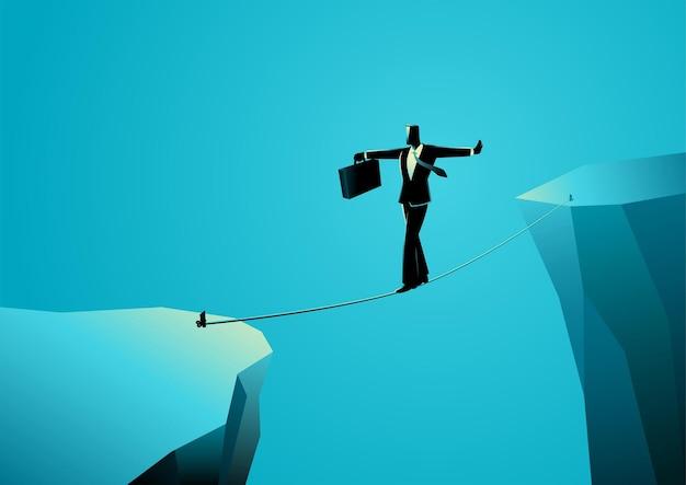 ギャップを越えるためにロープを歩くビジネスマン