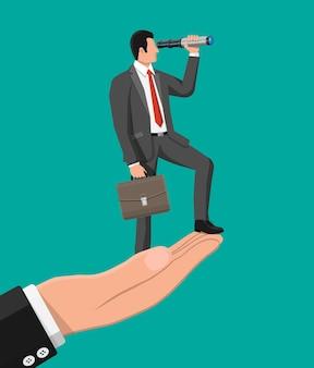 Бизнесмен с портфелем под рукой ищет возможности в подзорную трубу.