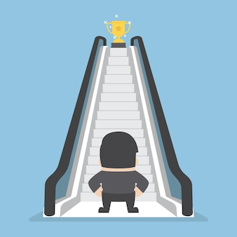 Businessman with escalator that leads the trophy