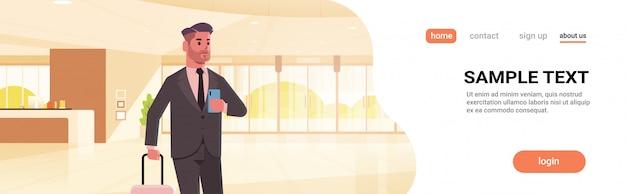 ロビーのモダンなホテルのホールのインテリアに立っているスーツケース男を保持している荷物モダンなレセプションエリアビジネス男を持ったビジネスマン