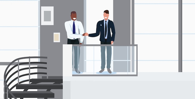 Businessmen couple shaking hands mix race partners handshaking during meeting agreement partnership concept modern office interior