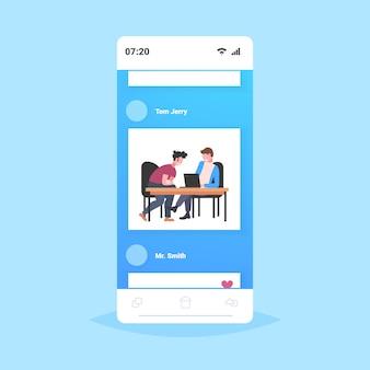 ラップトップの作業プロセスチームワークの概念のスマートフォンの画面のモバイルアプリの全長を使用して、職場の机に座っているビジネスマンの同僚2人のビジネスマン