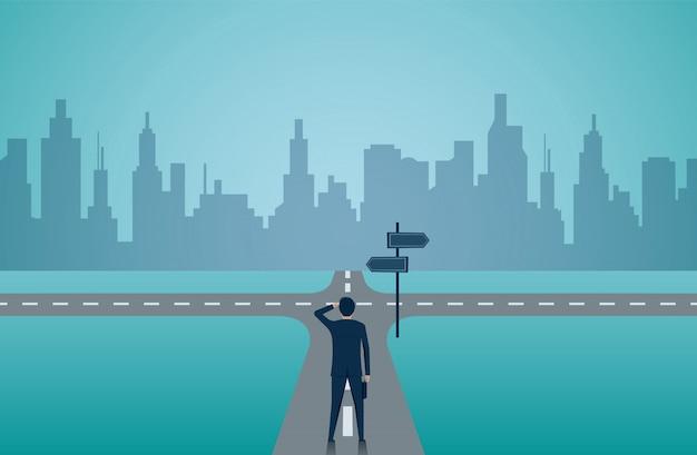 道路上の交差点に立っているビジネスマン。