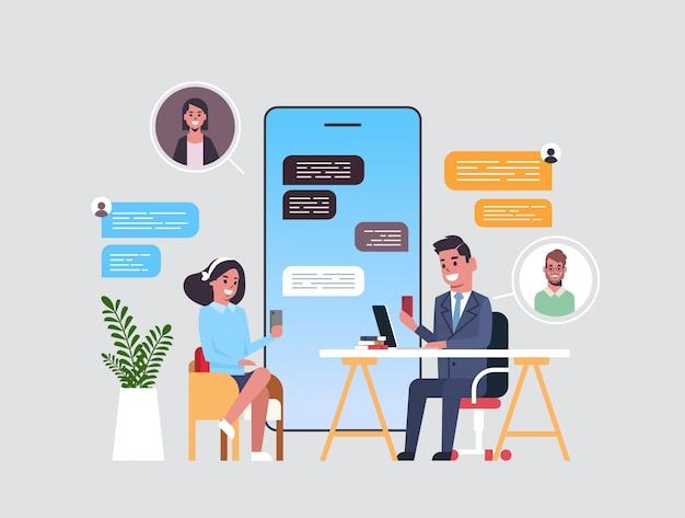 ビジネスマンのカップルがデジタルデバイスでチャットアプリを使用してソーシャルネットワークチャットバブル通信の概念