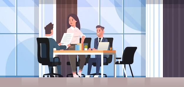 Деловые люди обсуждают контракт во время развития бизнеса встречаются коллеги партнеры работают с интерьером офиса переговоров по соинвестированию документов