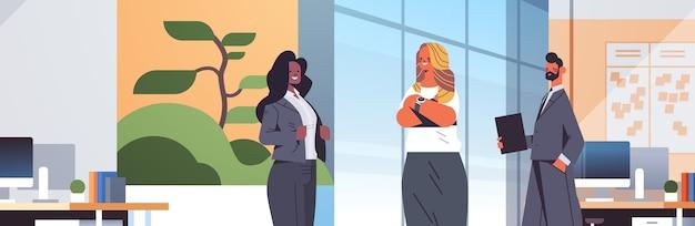 現代のオフィスのインテリアイラストと一緒に立っているビジネスコミュニケーションの概念ミックスレースの同僚との会議中に議論するビジネスマン