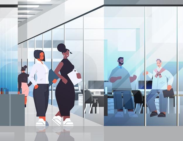会議中に話し合うビジネスマンビジネスコミュニケーションの概念は、オフィスで働くレースの同僚の完全な長さの図