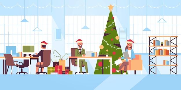 職場に座っているサンタのビジネスマンメリークリスマス新年あけましておめでとうございます休日お祝いコンセプトモダンなオープンスペースオフィスインテリアフラットイラスト