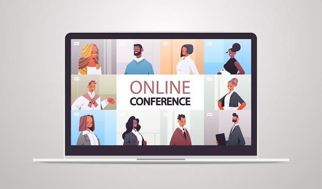 ノートパソコンの画面の図でグループビデオ通話によって作業している企業のオンライン会議ミックスレースチームの間に議論しているwebブラウザウィンドウのビジネスマン