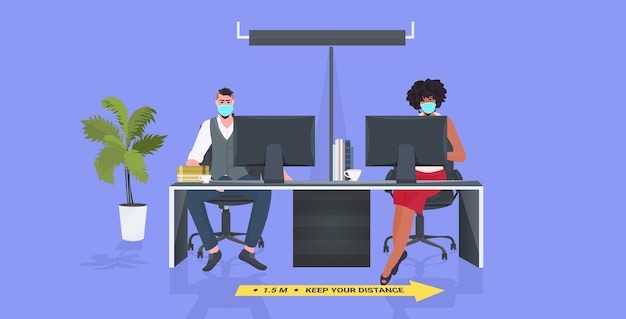 Businesspeople in masks sitting at workplace keeping distance to prevent coronavirus epidemic