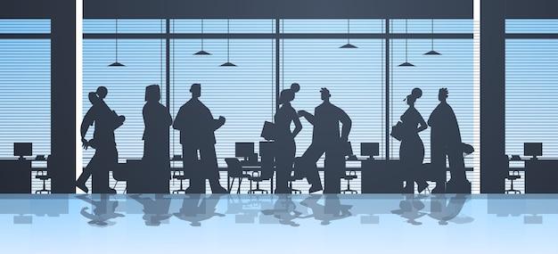 チームワークの概念の完全な長さの図を会議中に議論するオフィスビジネスの人々のグループで働くビジネスマンのシルエット