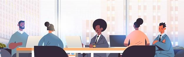 Бизнесмены, сидящие за круглым столом, смешанная гонка, команда деловых людей, обсуждающая во время конференции, интерьер современного офиса, иллюстрация