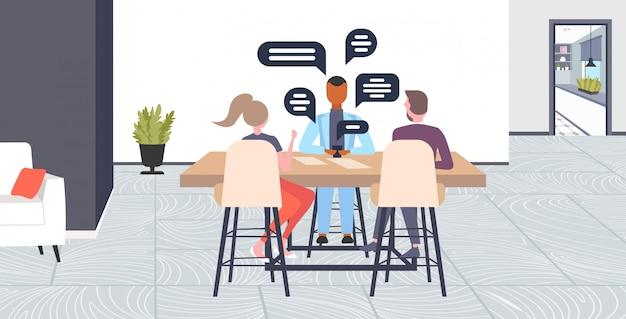 Бизнесмены, сидя за столом, обсуждая во время кофе-брейк социальной сети чат пузырь связи концепция