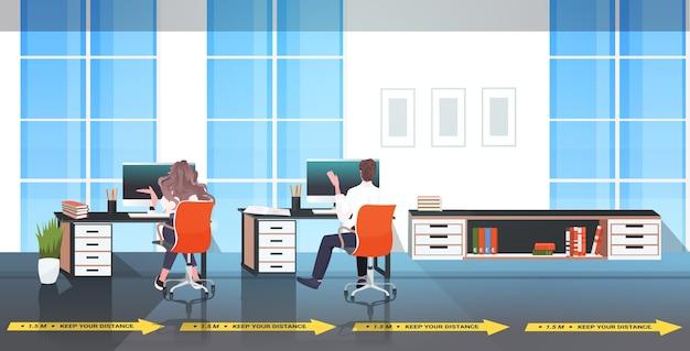 コロナウイルスの流行を防ぐために距離を置いて職場の机に座っているビジネスマン-19保護対策