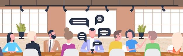 Бизнесмены сидя счетчик стол в чате во время кофе-брейк социальной сети чат пузырь связи концепция