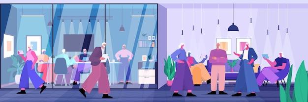 현대 사무실 수평 전체 길이 벡터 일러스트 레이 션에서 디지털 가제트를 사용하여 비즈니스 사람들 그룹과 함께 일하는 기업인 팀