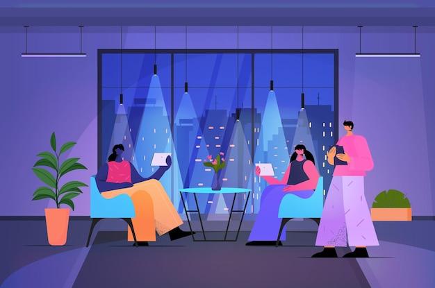 Бизнесмены, использующие цифровые гаджеты, деловые люди, работающие в современном темном ночном офисе по горизонтали