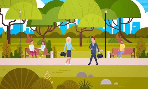 벤치에 앉아 의사 소통하는 자연 속에서 편안한 사람들을 통해 도시 공원에서 산책하는 비즈니스맨