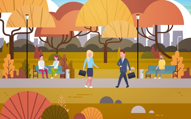 Businesspeople walking through autumn park over people having rest relaxing sit on bench and communicate outdoors