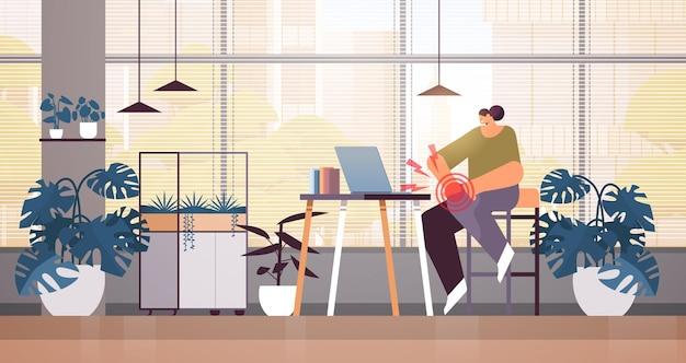 Бизнесвумен на рабочем месте страдает от боли в колене, воспаления мышц, концепция болезненной воспаленной области, выделенной красным цветом, офисный интерьер, горизонтальная полная длина, векторная иллюстрация