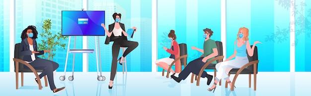 オフィスコロナウイルスパンデミックコンセプト水平での会議会議中に混血ビジネスマンチームと話し合うマスクの女性実業家