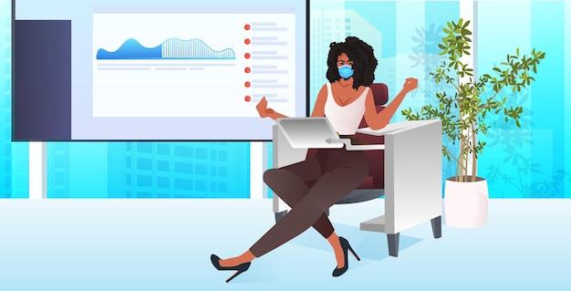 직장에 앉아 노트북 코로나 바이러스 유행성 개념 현대 사무실 인테리어 수평을 사용하는 마스크 사업가
