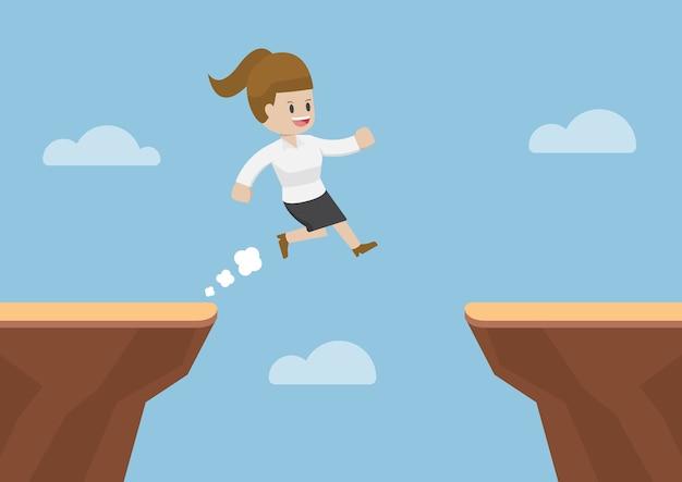 Деловая женщина прыгает через пропасть между утесами
