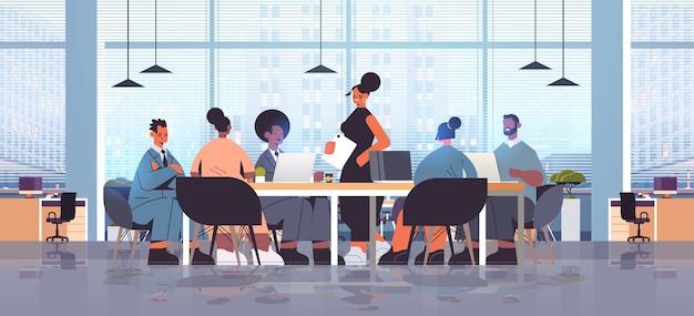 円卓会議での会議中に混血のビジネスマングループと話し合う実業家のリーダーモダンなオフィスインテリア全身イラスト