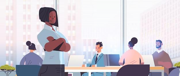 混血のビジネスマンの同僚の前に立って会議会議中に現代のオフィスのインテリアイラストを議論する実業家のリーダー