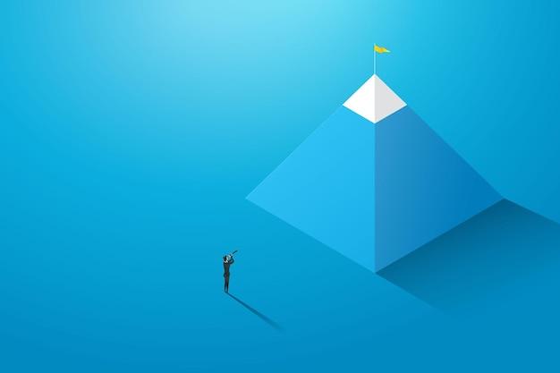 Деловая женщина смотрит на цель на склоне холма в бинокль