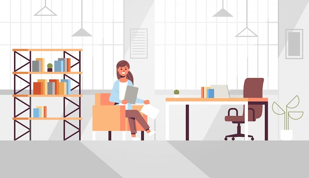 Businesswoman sitting at workplace desk business woman holding paper documents preparing report working process modern office interior
