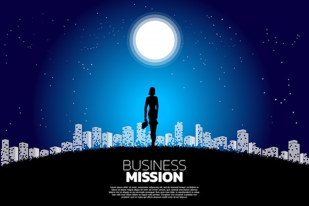 Businesswoman standing in the moon in light of city.