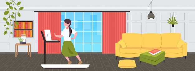 Businesswoman using laptop running on treadmill woman freelancer workout hard working concept modern living room interior  full length horizontal