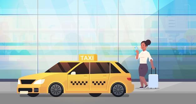 黄色いタクシー都市交通サービスコンセプト全長水平近く荷物とフォーマルな服装でストリートビジネス女性にタクシーを注文するモバイルアプリを使用して実業家