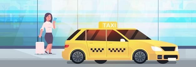 黄色のタクシーの都市交通サービスの近くの荷物とフォーマルな服装でストリートビジネス女性にタクシーを注文するモバイルアプリを使用して実業家