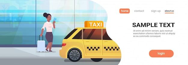 黄色いタクシー都市輸送サービスコンセプト全長コピースペース水平近くの荷物を持つストリートビジネス女性にタクシーを注文するモバイルアプリを使用して実業家