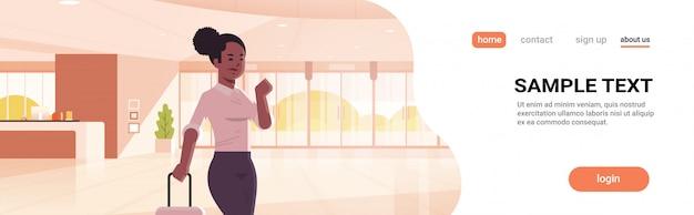 現代的なロビーホテルホールのインテリアに立っているスーツケースの女の子を保持しているフロントエリアアフリカ系アメリカ人ビジネス女性でモダンな荷物を持つ実業家