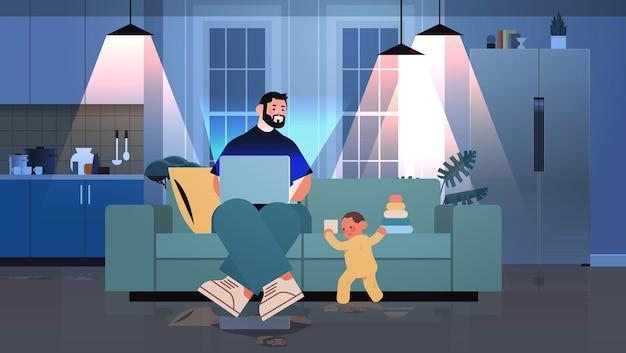 노트북을 사용하여 집에서 일하는 바쁜 아버지 프리랜서 어린 아들이 장난감을 가지고 노는 프리랜서 아버지 개념 어두운 밤 거실 내부 전체 길이 수평