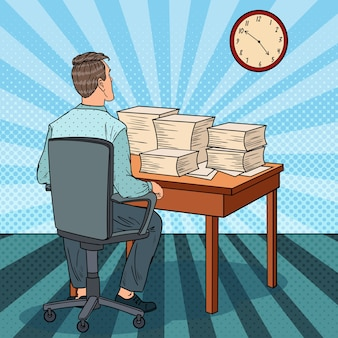 Busy office worker with piles of papers