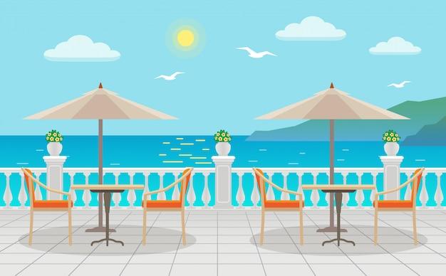 通りに海の景色を望む傘の下のテーブルのあるカフェ