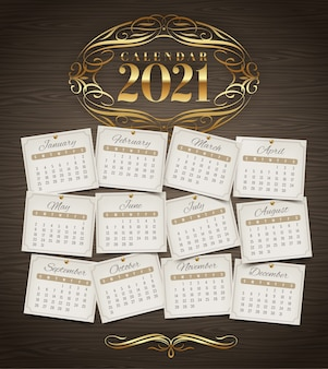 Calendar for 2021 year with golden flourishes elements on a wooden background
