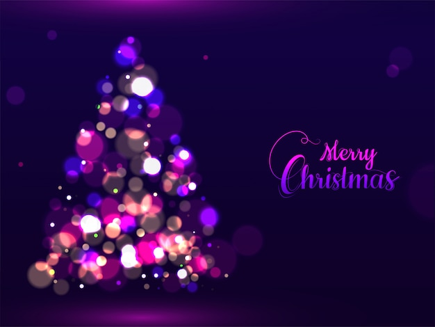Calligraphy of merry christmas and creative xmas tree made by bokeh effect on purple   greeting card .
