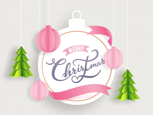 Calligraphy merry christmas text in bauble shape frame decorated with paper cut xmas tree and ornament balls on white background