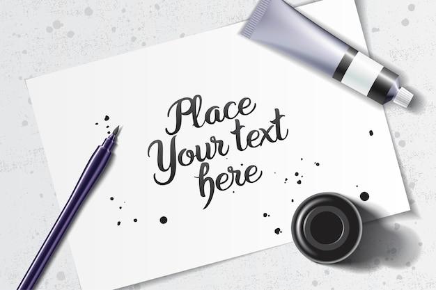白い紙とグランジテーブルのスペースにブラシペンと黒のインクボトルと書道のモックアップ