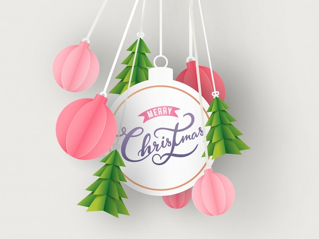 Calligraphy text merry christmas in bauble shape frame with hanging paper cut xmas tree and ornament balls decorated on white background.