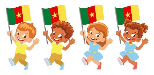Флаг камеруна в руке. дети держат флаг. государственный флаг камеруна
