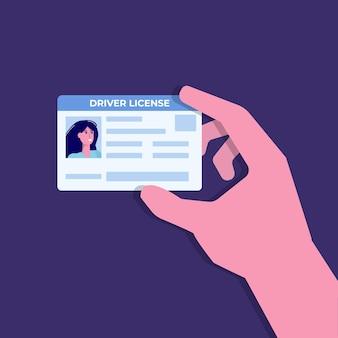 車の運転免許証を手に。idカードを持っている。