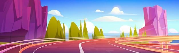 Strada del cavalcavia dell'automobile sulla riva del mare con montagne e alberi verdi