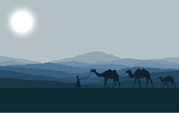 Caravan with camels in desert with mountains on background.