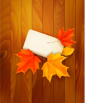 Card with leaves on wooden background. .